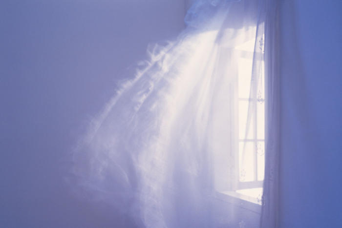 Open windows with billowy curtains